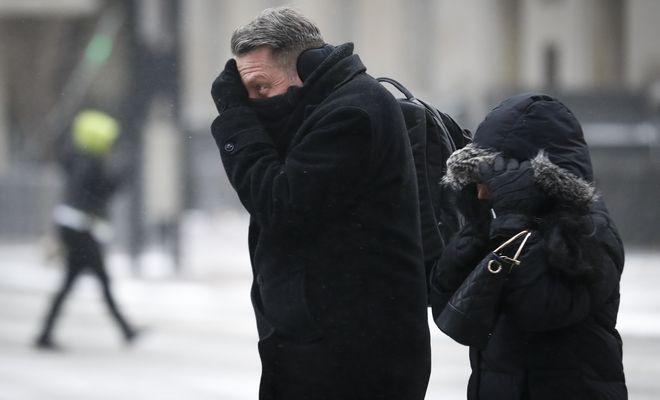 Πεζοί προσπαθούν να προστατευτούν από τον παγωμένο αέρα