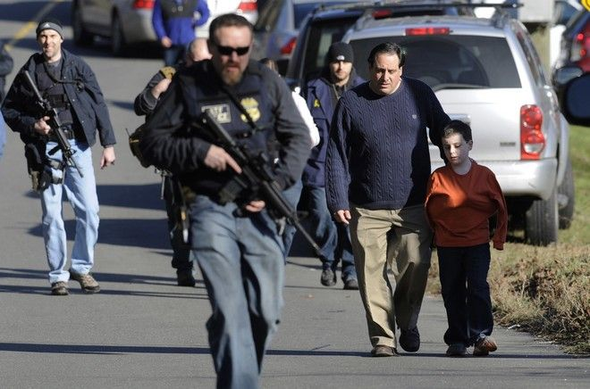 FILE - In this Friday, Dec. 14, 2012 file photo, parents leave a staging area after being reunited with their children following a shooting at the Sandy Hook Elementary School in Newtown, Conn., where Adam Lanza fatally shot 27 people, including 20 children. On Wednesday, Dec. 14, 2016, Newtown is planning to mark the fourth anniversary of the Sandy Hook Elementary School shooting with a moment of silence. (AP Photo/Jessica Hill, File)