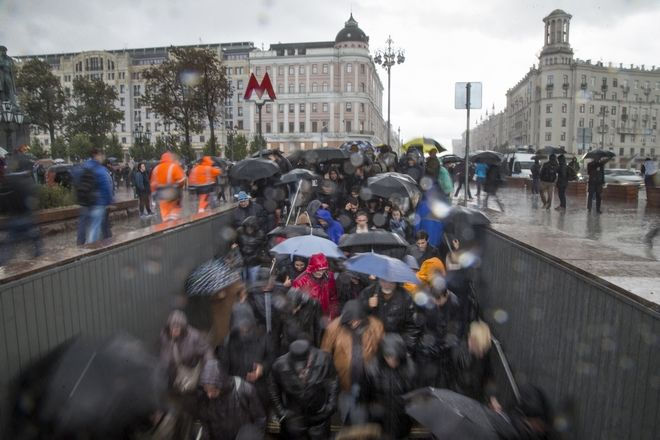 Demonstrators walk down into a subway under heavy rain during a rally in Moscow, Russia, Saturday, Oct. 7, 2017. Supporters of opposition leader Alexei Navalny rallied across Russia on Saturday, heeding his call to pressure authorities into letting him enter the presidential race with a wave of demonstrations on President Vladimir Putin's 65th birthday. (AP Photo/Ivan Sekretarev)