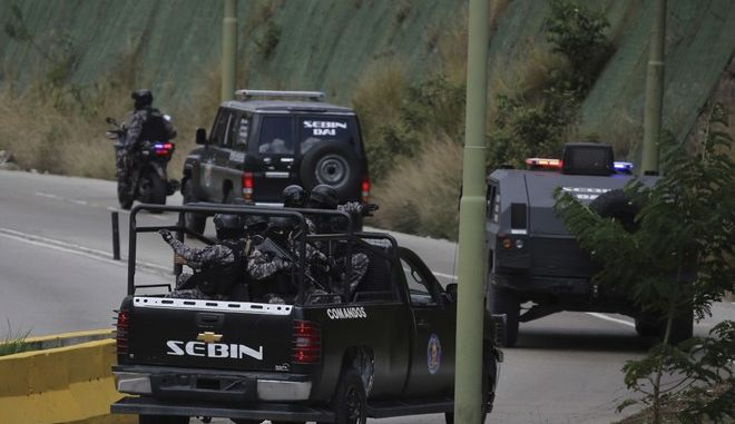 Members of the Venezuelan Bolivarian Intelligence Service arrive to the Junquito highway during an operation to capture Oscar Perez, according to officials, in Caracas, Venezuela, Monday, Jan. 15, 2018. Venezuelan special forces exchanged gunfire Monday with the rebellious police officer who has been on the run since leading a high-profile attack in Caracas last year, officials said. (AP Photo/Fernando Llano)