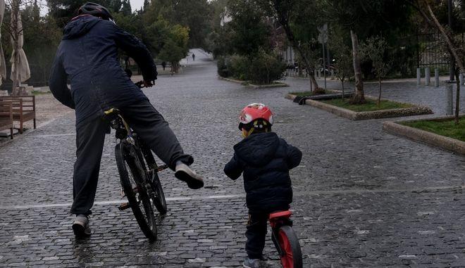 Πατέρας και παιδί κάνουν ποδήλατο στην εποχή της καραντίνας