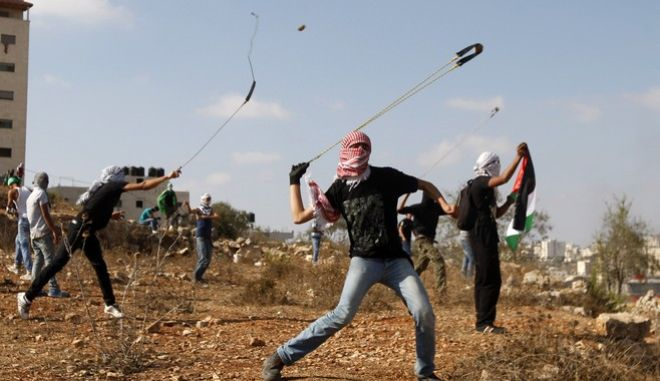 "Palestinians  throw stones during clashes with Israeli soldiers on the 13th anniversary of the second Palestinian ""Intifada"", or uprising against Israeli occupation, outside Ofer, an Israeli military prison near the West Bank city of Ramallah, Friday, Sept 27, 2013. (AP Photo/Majdi Mohammed)"