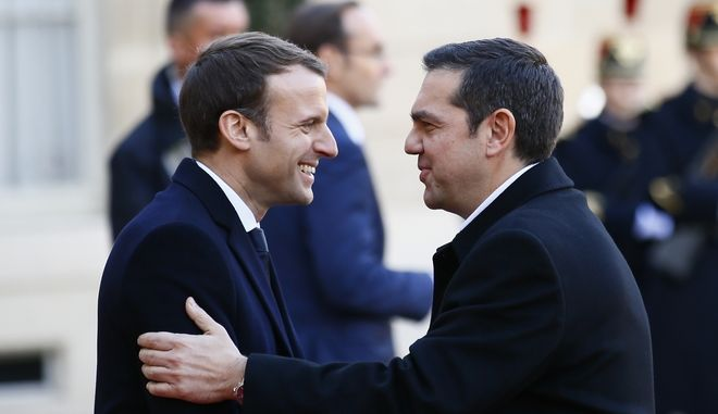 Greece's Prime Minister Alexis Tsipras is welcomed by French President, left, before a lunch at the Elysee Palace in Paris, Tuesday, Dec. 12, 2017. More than 50 world leaders are gathering in Paris for a summit that Macron hopes will give new momentum to the fight against global warming, despite U.S. President Donald Trump's rejection of the Paris climate accord. (AP Photo/Francois Mori)