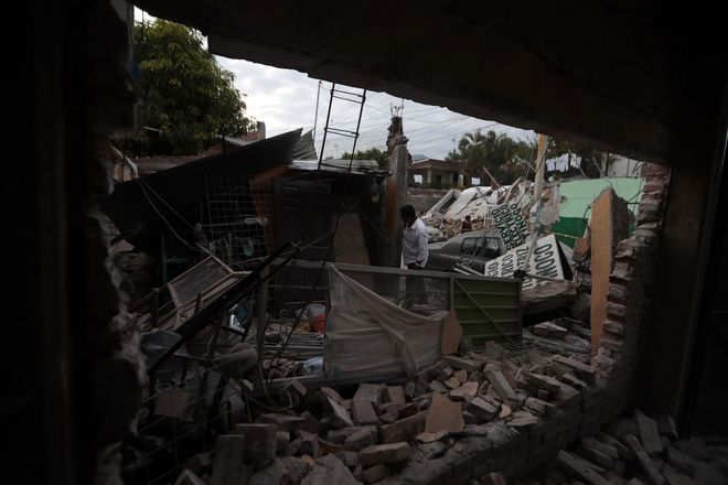 A man surveys a building demolished by a 7.1 earthquake, in Jojutla, Morelos state, Mexico, Wednesday, Sept. 20, 2017. Police, firefighters and ordinary Mexicans are digging frantically through the rubble of collapsed schools, homes and apartment buildings, looking for survivors of Mexico's deadliest earthquake in decades as the number of confirmed fatalities climbed to 248. (AP Photo/Eduardo Verdugo)