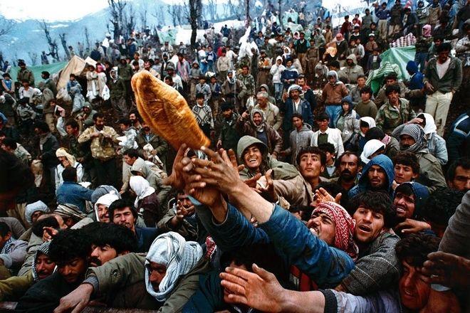 Κούρδοι πρόσφυγες αγωνίζονται να πάρουν ένα κομμάτι ψωμί κατά τη διάρκεια της διανομής ανθρωπιστικής βοήθειας στα σύνορα Ιράκ-Τουρκίας.