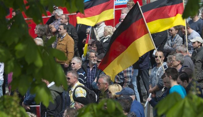People hold flags during a demonstration initiated by Germany's nationalist party AfD (Alternative for Germany) on the May Day in Erfurt, central Germany, Monday, May 1, 2017. (AP Photo/Jens Meyer)
