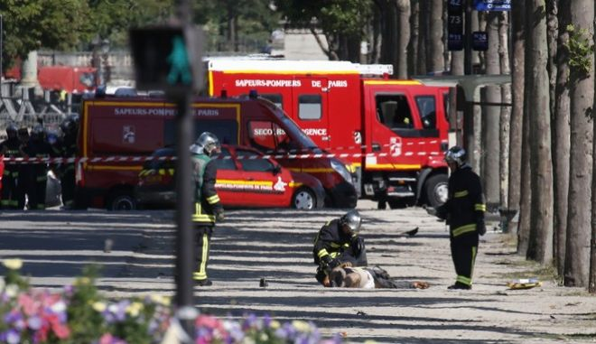 Rescue workers examine a body lying on the Champs Elysées in Paris, Monday, June 19, 2017. A driver rammed his car, partially seen at left behiong the police van, into a police vehicle in the Champs-Elysees shopping district Monday, prompting a fiery explosion, and was likely killed in the incident, authorities said. France's anti-terrorism prosecutor opened an investigation. (AP Photo/Thibault Camus)