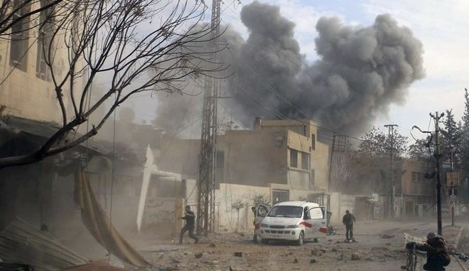 This photo provided by the Syrian Civil Defense White Helmets, which has been authenticated based on its contents and other AP reporting, shows a plume of smoke rises while civil defense workers arrive at the scene of an attack after airstrikes hit a rebel-held suburb near Damascus, Syria, Thursday, Feb. 8, 2018. Syrian rescue workers and activists say the death toll from ongoing government strikes on the opposition-held region near the capital Damascus has risen to at least 35. (Syrian Civil Defense White Helmets via AP)