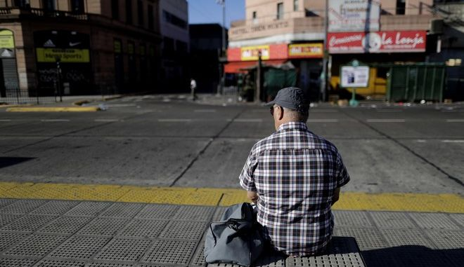 A man sits at the bus stop in Constitution station in Buenos Aires, Argentina, Thursday, April 6, 2017. A national strike, the first in the era of Mauricio Macri's government, has forced all public transports services to not work Thursday. (AP Photo/Natacha Pisarenko)