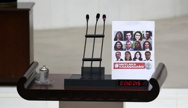 A placard with photos of 11 jailed pro-Kurdish Peoples' Democratic Party, HDP, lawmakers, left by Leyla Birlik, a HDP lawmaker, after she addressed as Turkey's parliament debate proposed amendments to the country's constitution that would hand President Recep Tayyip Erdogan's largely ceremonial presidency sweeping executive powers, in Ankara, Turkey, early Thursday, Jan. 19, 2017.  (AP Photo)