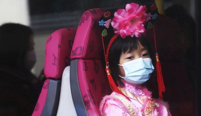 Κορίτσι με μάσκα σε λεωφορείο του Χονγκ Κονγκ