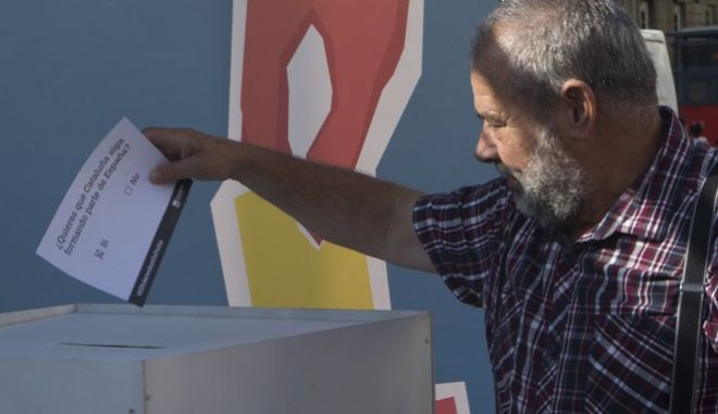 "A man casts a symbolic 'No' vote during protest against the Catalonian referendum in Madrid, Spain, Friday, Sept. 29, 2017. Despite the heated debate surrounding a planned referendum on whether Catalonia should secede from the rest of Spain, the ""yes"" side is campaigning mostly unopposed, because those who are against Catalan independence say they don't plan to vote at all. The voting paper reads ' Do you want Catalonia to remain part of Spain?' (AP Photo/Paul White)"