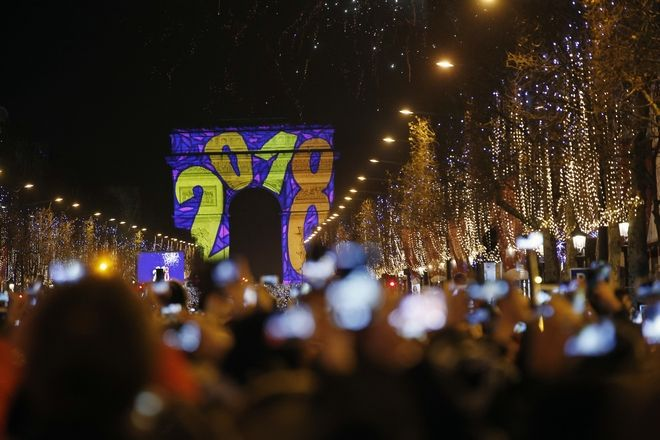 People celebrate New Year at the Arc de Triomphe as the firework explode over it, on the Champs Elysees, in Paris, France, Monday, Jan. 1, 2018. (AP Photo/Thibault Camus)