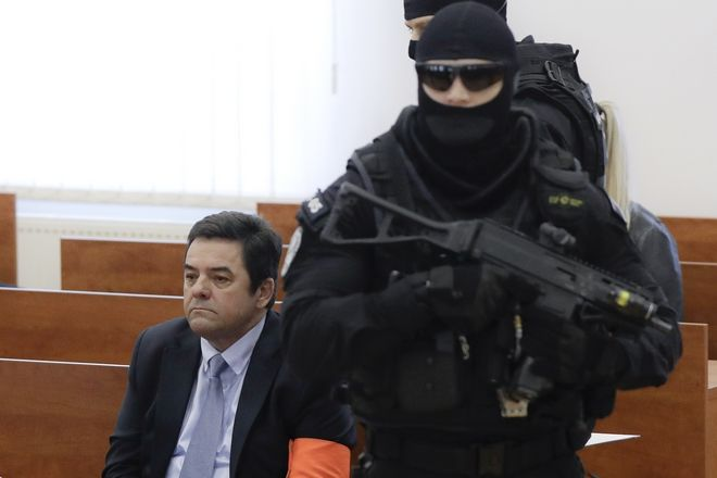 Marian Kocner sits surrounded by armed police officers in a courtroom ahead of the trial in Pezinok, Slovakia, Thursday, Dec. 19, 2019. The trial opened on Thursday with, Marian Kocner, the suspected mastermind in the slaying of an investigative journalist Jan Kuciak and his fiancee Martina Kusnirova , who were shot dead in their home on Feb. 21, 2018, a case that has shocked the nation and shaken the country's politics. (AP Photo/Petr David Josek)