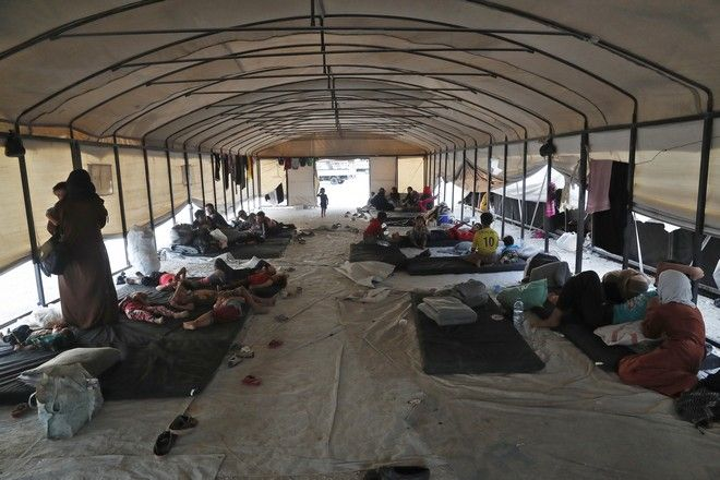 Syrian displaced families who fled the battle between U.S.-backed Syrian Democratic Forces (SDF) and the Islamic State militants from Raqqa city, sit inside a transfer tent as they wait to receive a private tent upon their arrival at a refugee camp, in Ain Issa town, northeast Syria, Monday, July 24, 2017. The U.S. military is supporting local Syrian forces in a campaign to drive IS from Raqqa. (AP Photo/Hussein Malla)