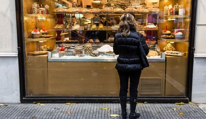 A woman looks at the patisserie shop window in a commercial street in the center of northern Greece city of Thessaloniki./            .
