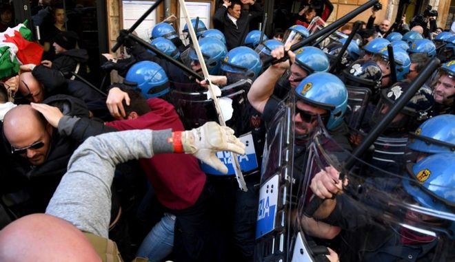 Riot police clash with taxi drivers and street sellers during a demonstration, in Rome, Tuesday, February 21, 2017. A weeklong strike by taxi drivers that has crippled transport in Rome, Milan and Turin is heating up, with cabbies marching through the eternal city to protest legislation they say will favor Uber and other car-hire services.  (Alessandro Di Meo/ANSA via AP)