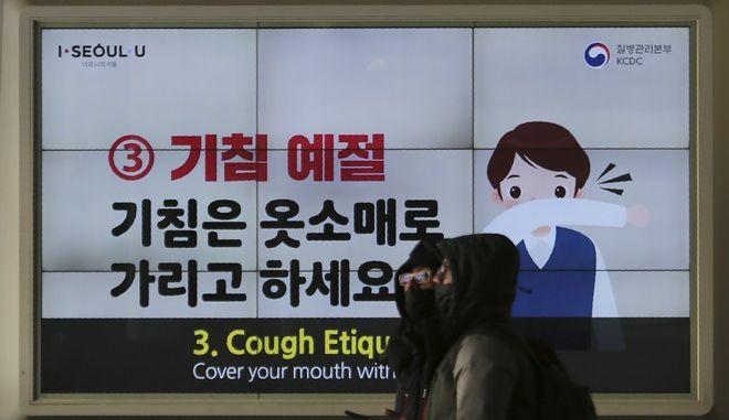 Νοτιοκορεάτες που φορούν μάσκες περπατούν μπροστά από μια πινακίδα με οδηγίες πρόληψης για τον νέο κοροναϊό