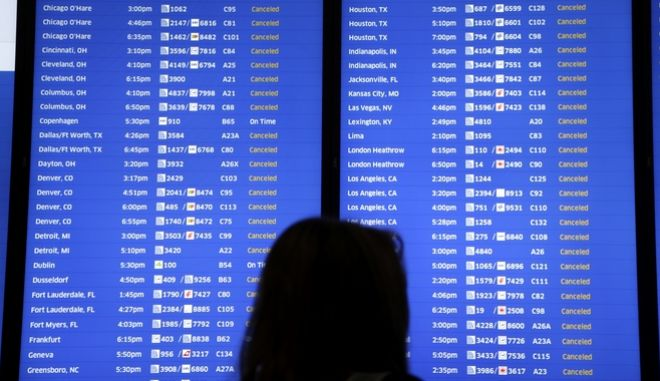 People look at a display that shows mostly cancelled flights at Newark Liberty International Airport in Newark, N.J., Thursday, Jan. 4, 2018. Residents across a huge swath of the U.S. awakened Thursday to the beginnings of a massive winter storm expected to deliver snow, ice and high winds followed by possible record-breaking cold as it moves up the Eastern Seaboard from the Carolinas to Maine. (AP Photo/Seth Wenig)