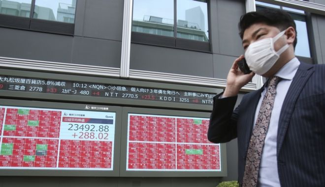 Άνδρας μπροστά από ηλεκτρονικό πίνακα χρηματιστηρίου στο Τόκιο