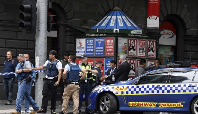 Police listen to witnesses near the site where a car struck pedestrians in the central business district of Melbourne, Australia, Friday, Jan. 20, 2017. A man deliberately drove into a street crowded with pedestrians on Friday, killing people, police said. Officials said the incident had no links to terrorism. (AP Photo/Andrew Brownbill)