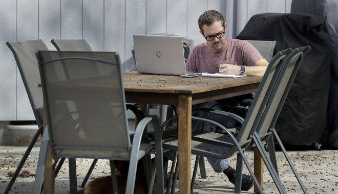 Erik Wray works on his computer in the backyard of his home Thursday, March 19, 2020, in Overland Park, Kan. Wray, a program manager for the Alzheimer's Association - Heart of America chapter, is among millions of workers toiling from home in an attempt to stem the spread of the coronavirus. (AP Photo/Charlie Riedel)