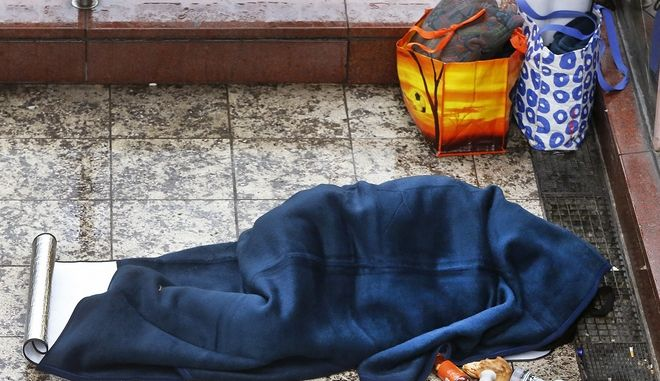 A homeless person sleeps under his blanket in downtown Frankfurt, Germany, on a cold and rainy Wednesday, Jan. 4, 2017. (AP Photo/Michael Probst)