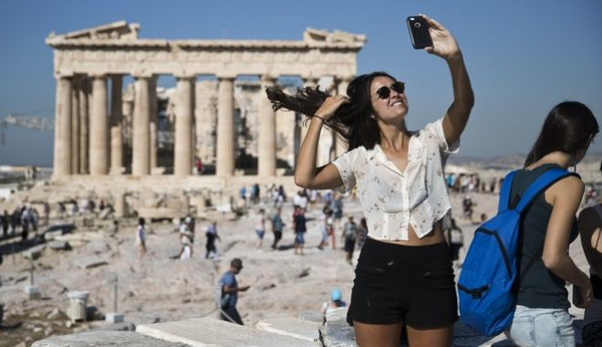 A tourist takes a selfie in front of the the ruins of the fifth century B.C. Parthenon temple at the Acropolis hill, on Friday, Sept. 1, 2017. Greece's national statistics authority says the country's economy grew by 0.8 percent in the second quarter of 2017 compared to the same quarter last year, provisional data of seasonally adjusted figures show. (AP Photo/Petros Giannakouris)