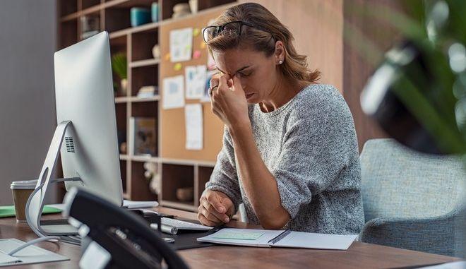 Γυναίκα εργαζόμενη νιώθει εξαντλημένη στο γραφείο της