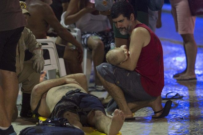 A man holds a baby next to an injured man after a car drove into the crowded seaside boardwalk along Copacabana beach in Rio de Janeiro, Brazil, Thursday, Jan. 18, 2018. Military police said on Twitter that at least 11 people were injured and that the driver has been taken into custody. (AP Photo/Silvia Izquierdo)