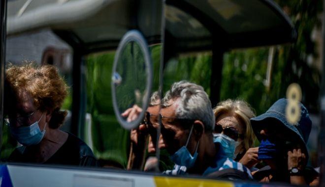 Άνθρωποι με μάσκες σε λεωφορείο της Αθήνας.