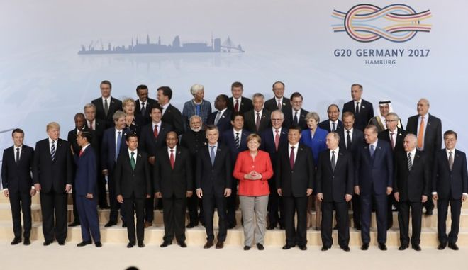 The participants pose for a group photo on the first day of the G-20 summit in Hamburg, northern Germany, Friday, July 7, 2017. The leaders of the group of 20 meet July 7 and 8. (AP Photo/Michael Sohn)