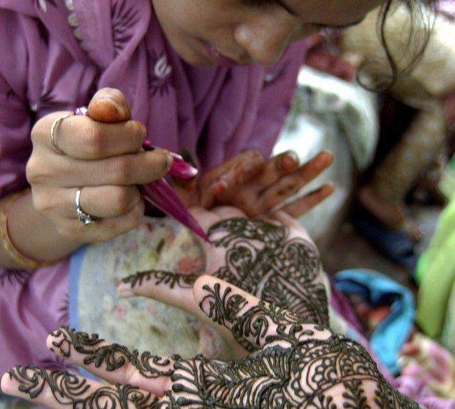 Μια νέα γυναίκα κάνει εφαρμογή χένας στα χέρια κοριτσιού, στο πλαίσιο του φεστιβάλ Teej του Νέου Δελχί, τον Αύγουστο του 2003.