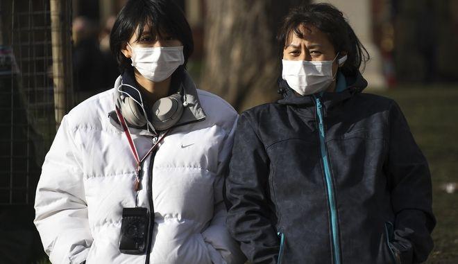 Πολίτες φορούν μάσκες.