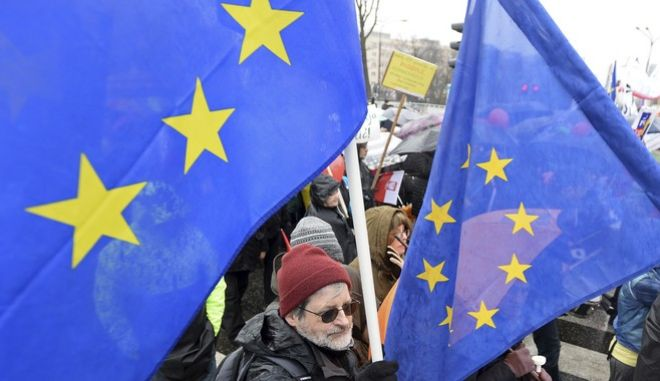 Protesters carry European Union flags as they walk through downtown streets in a march against government plans of curbing the power of local governments and of submitting the judiciary to the ruling party's control in Warsaw, Poland, Saturday, March 18, 2017. Hundreds of people, braving cold and rain attended the demonstration organized by the civic opposition group, the Committee for the Defense of Democracy. (AP Photo/Alik Keplicz)