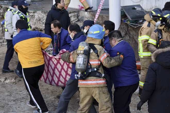Rescue teams carry a body from a hospital fire in Miryang, South Korea, Friday, Jan. 26, 2018. A fire swept through the hospital in southeastern South Korea on Friday, killing more than 30 people and injuring dozens in one of the country's most deadly fires in recent years. (Kim Gu Yeon/Gyeongnam Domin Ilbo via AP)