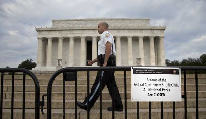 "A US Park Police officer walks behind a barricade with sign reading ""Because of the Federal Government SHUTDOWN All National Parks are Closed"" in front of the Lincoln Memorial in Washington, Tuesday, Oct. 1, 2013. Congress plunged the nation into a partial government shutdown Tuesday as a long-running dispute over President Barack Obama's health care law stalled a temporary funding bill, forcing about 800,000 federal workers off the job and suspending most non-essential federal programs and services. (AP Photo/Carolyn Kaster)"