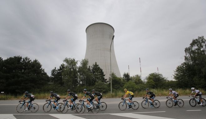 The pack led by team Sky with Britain's Christopher Froome, wearing the overall leader's yellow jersey, passes the Tihange nuclear plant during the fourth stage of the Tour de France cycling race over 223.5 kilometers (138.9 miles) with start in Seraing, Belgium, and finish in Cambrai, France, Tuesday, July 7, 2015. (AP Photo/Christophe Ena)