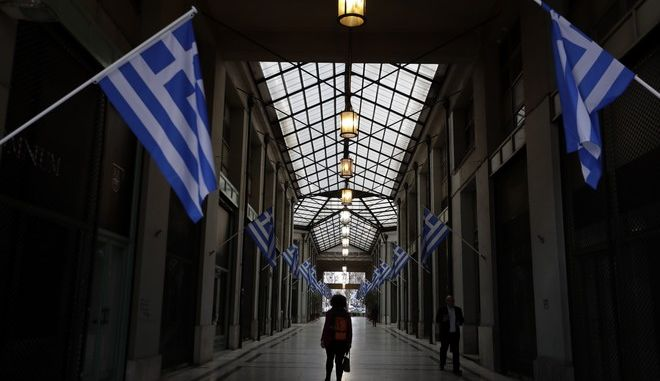 In this photo taken on Wednesday, March 22, 2017 a woman passes a shopping arcade with Greek flags, where shops closed because of the crisis in central Athens. Over the past seven years, austerity has left visible scars in Greeces capital. A walk around Athens reveals more homeless than ever despite some signs of a rosier economic outlook. Thousands of shops, mostly small businesses, are shuttered here and across the country. In what used to be a busy shopping arcade, closed stores are padlocked against a backdrop of hanging Greek flags. (AP Photo/Thanassis Stavrakis)