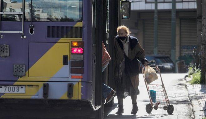 Ηλικιωμένη με μάσκα επιβιβάζεται σε τρόλεϊ της Αθήνας