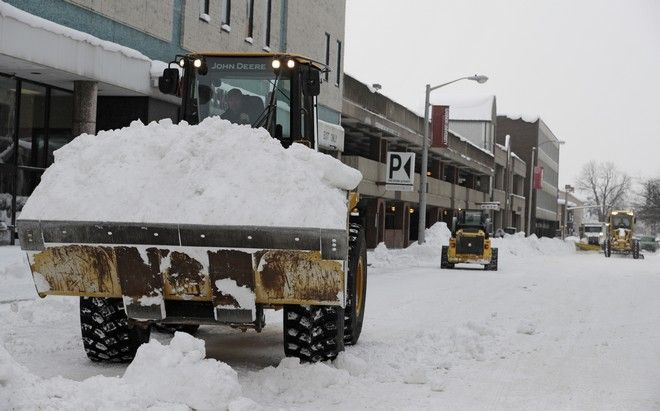 Workers clear streets, Friday, Dec. 29, 2017, in downtown Erie, Pa. The cold weather pattern was expected to continue through the holiday weekend and likely longer, according to the National Weather Service, prolonging a stretch of brutal weather blamed for several deaths, crashes and fires. (AP Photo/Tony Dejak)