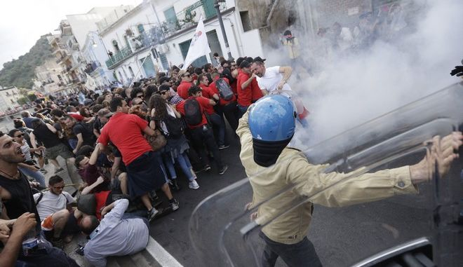 Demonstrators back after a short contact with police during an anti-G7 rally near the venue of the G7 summit in the Sicilian town of Taormina, Italy, Saturday, May 27, 2017. A summit of the leaders of the world's wealthiest democracies has ended without a unanimous agreement on climate change, as the Trump administration plans to take more time to say whether the U.S. is going to remain in the Paris climate deal. (AP Photo/Gregorio Borgia)