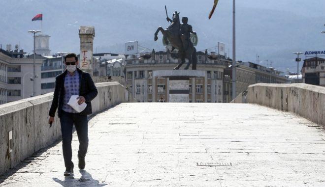 Ένας πολίτης με μάσκα και προστατευτικά γάντια διασχίζει έναν πολυσύχναστο δρόμο των Σκοπίων
