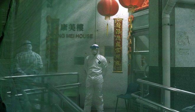 Ειδικό προσωπικό με προστευτικές στολές εκκενώνουν σπίτια στο Χονγκ Κονγκ