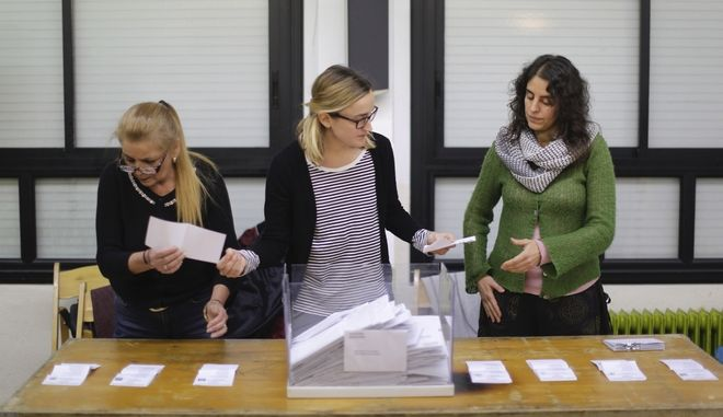 Polling station workers count votes for the Catalan regional election in Girona, Spain, on Thursday, Dec. 21, 2017. Catalans are choosing new political leaders in a highly contested election called by central authorities to quell a separatist bid in Spain's northeastern region. (AP Photo/Bernat Armangue)