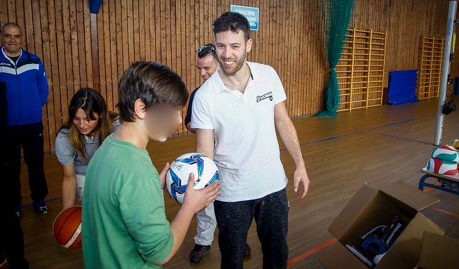 Ο πρωταθλητής του καράτε Γιώργος Τζάνος, μοιράζει αθλητικό υλικό της Stoiximan στους μαθητές της Ελευσίνας.