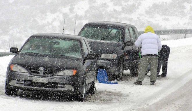 Οδηγοί περνούν αλυσίδες στα οχήματα εν μέσω χιονόπτωσης