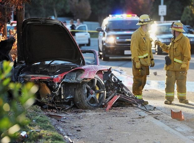 First responders gather evidence near the wreckage of a Porsche sports car that crashed into a light pole on Hercules Street near Kelly Johnson Parkway in Valencia on Saturday, Nov. 30, 2013. A publicist for actor Paul Walker says the star of the