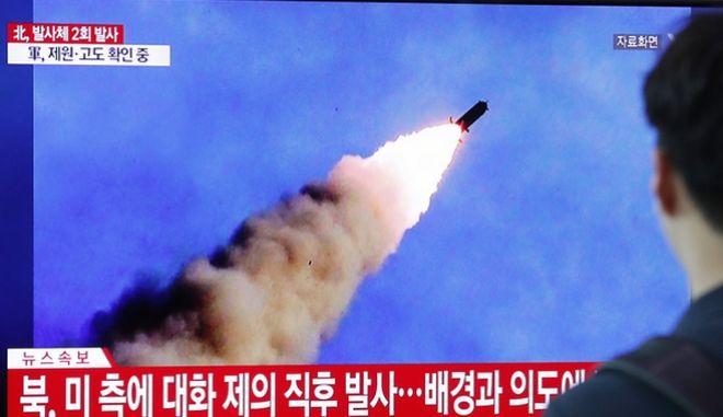 Πολίτες παρακολουθούν στις τηλεοράσεις την εκτόξευση πυραύλων.