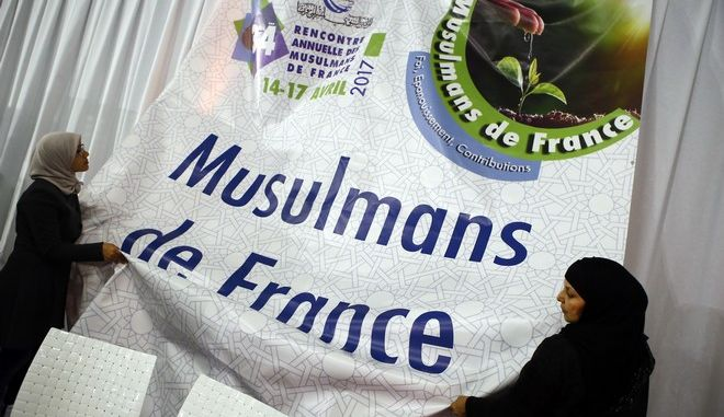 """Women help to adjust a banner reading """"Muslims of France"""" inside an exhibition hall at the France Muslim Annual Fair in Le Bourget, north of Paris, Saturday, April 15, 2017. Tens of thousands of Muslims are expected at the three-day event this weekend organized by the ultra-conservative Union of Islamic Organizations of France. It includes merchant stalls, Quran readings, prayers and speeches by leading Muslim figures as Muslims of France want to make sure their voices are heard in France's presidential elections. (AP Photo/Francois Mori)"""